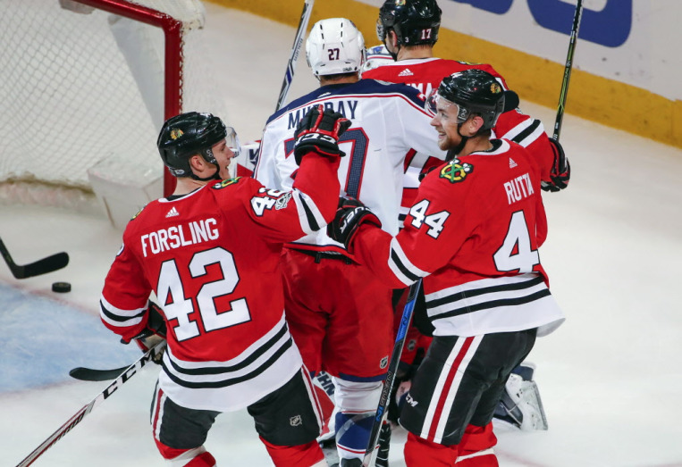 Chicago Blackhawks defenseman Jan Rutta (44) is congratulated by defenseman Gustav Forsling (42) after scoring against the Columbus Blue Jackets during the second period of an NHL hockey game Saturday, Oct. 7, 2017, in Chicago. (AP Photo/Kamil Krzaczynski) ORG XMIT: CXA109